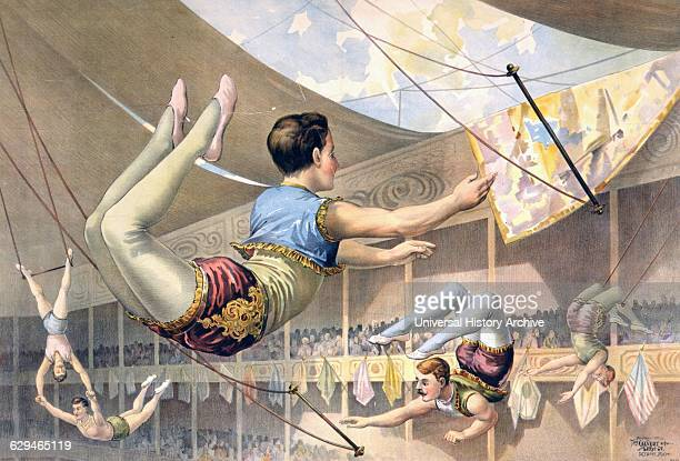 Five male trapeze artists performing at a circus c1890