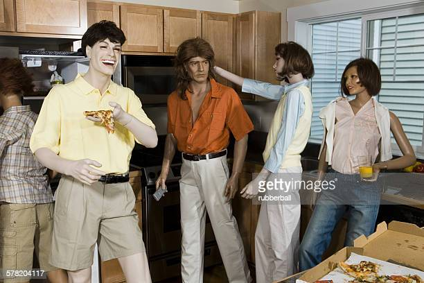 Five mannequins portraying a family in the kitchen