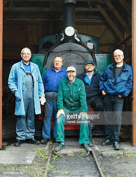 Five mature men wearing overalls, gathered by steam engine, portrait