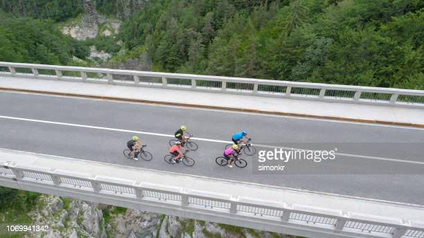 five men and women riding road bikes on bridge - road cycling stock pictures, royalty-free photos & images