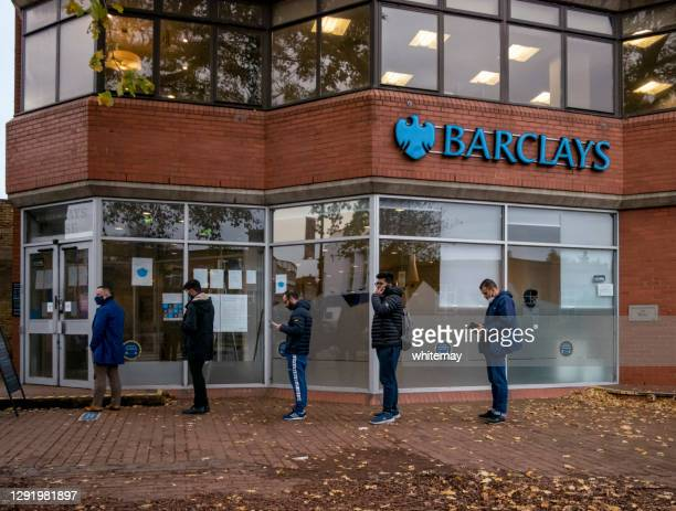 five men socially distanced outside barclays bank - barclays brand name stock pictures, royalty-free photos & images