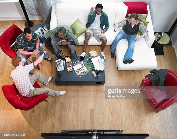 Five men watching television and cheering, elevated view