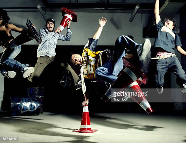 Five men with traffic cones jumping in midair