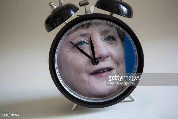 Five minutes before twelve for Chancellor Angela Merkel The photo shows a alarm clock with a Merkelportrait and the pointers to five minutes before...