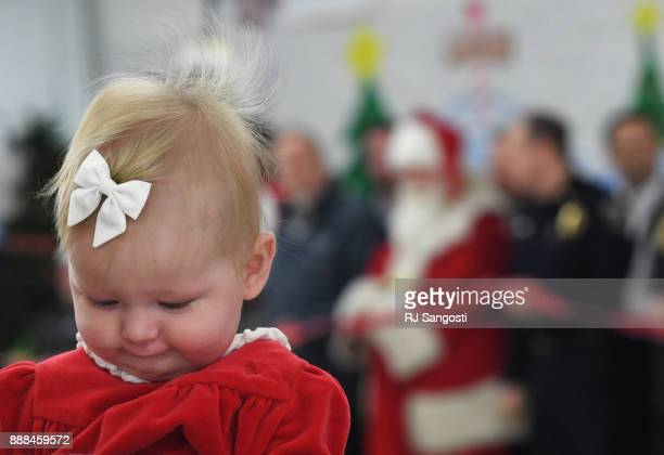 Five monthsold Millie Hill is held by her mother who waits with other supporters and volunteers for Santa to cut the ribbon to start this year annual...