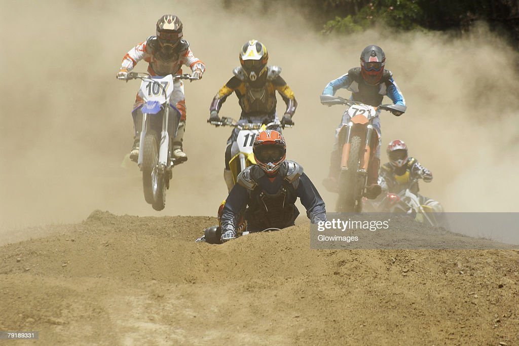 Five motocross riders riding motorcycles on a dirt road : Stock Photo