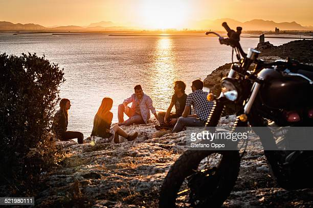 Five motorcycling friends taking a break on coast at sunset, Cagliari, Sardinia, Italy