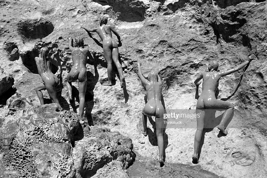 Five Mud Covered Nude Women Climb A Rocky Surface Stock -3572