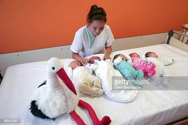 Five newborn babies in a row together with a pediatric nurse and a plush stork in the Asklepios Children's Hospital on July 13 2012 in St Augustin...