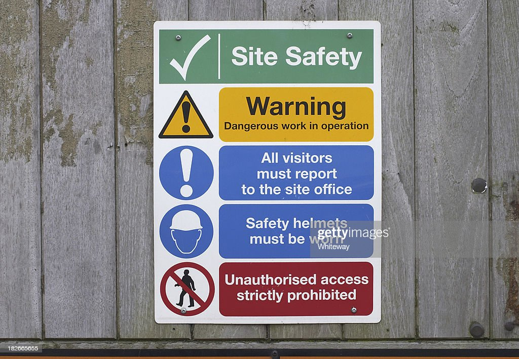 Construction site safety notices on wooden fence : Stock Photo