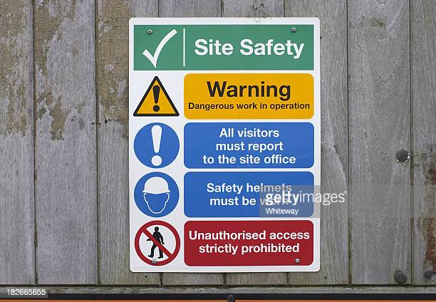 Construction site safety notices on wooden fence
