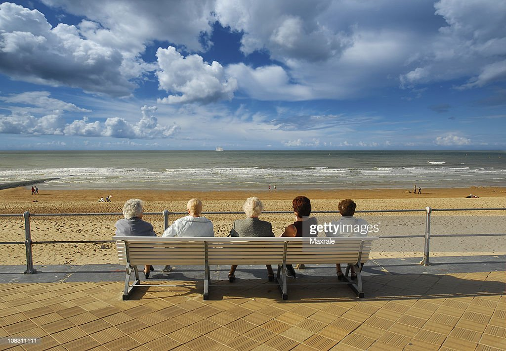 Five Old Ladies Sitting On Bench Chilling Out Near Sea Stock