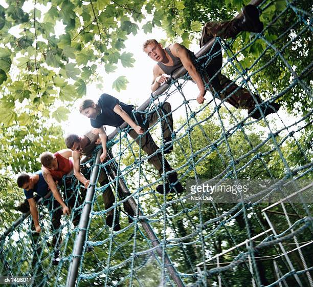 Five People Climbing Over a Net on an Assault Course