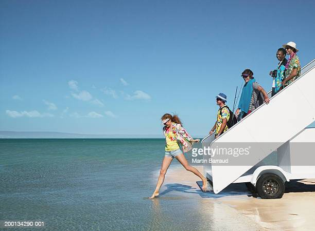 Five people descending aeroplane stairs into sea, side view