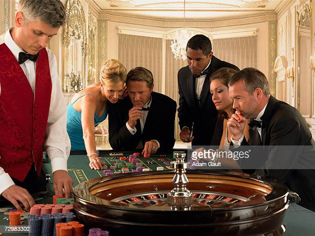 five people gambling beside croupier at roulette table - gambling table stock pictures, royalty-free photos & images