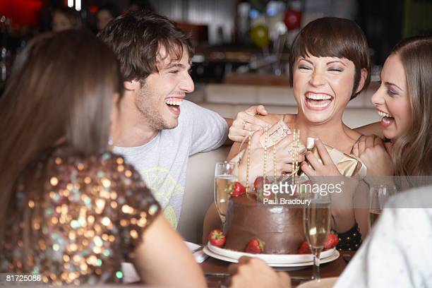 Five people having fun and laughing at a birthday party in a restaurant
