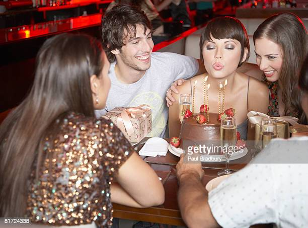 Five people having fun and smiling at a birthday party in a restaurant