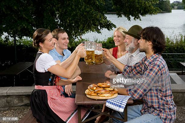 Five people in a beer garden toasting glasses