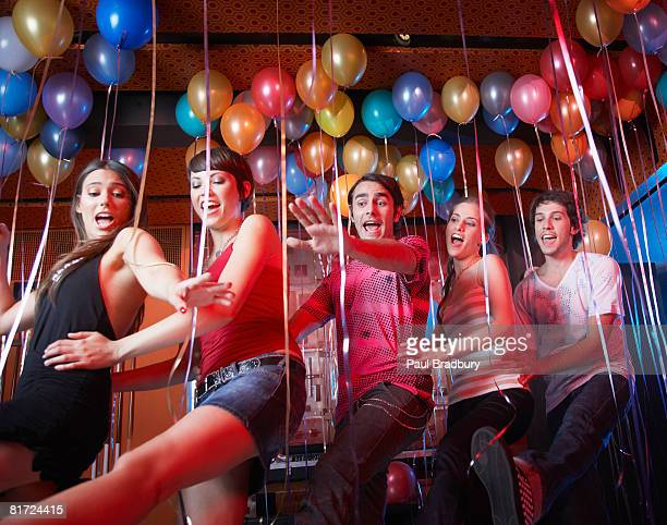 Five people in a nightclub dancing and smiling