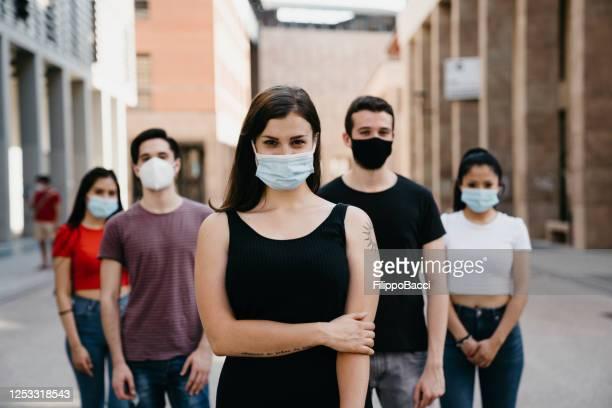cinco personas mirando a la cámara, usando máscaras faciales en la ciudad - adulto joven fotografías e imágenes de stock