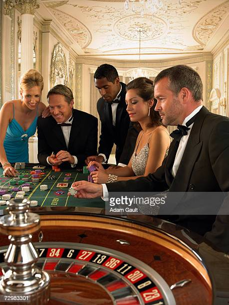 Five people placing bets at Roulette table in casino
