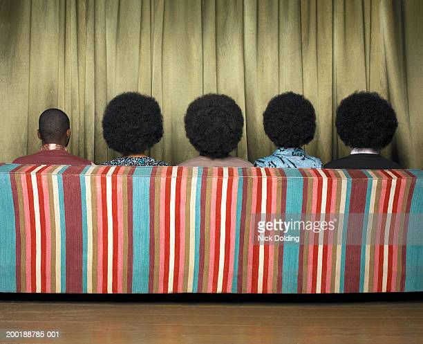 Five people sitting on sofa, rear view