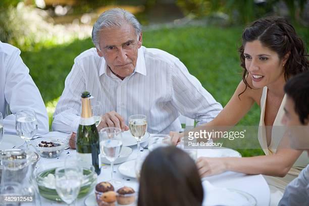 Cinco Pessoas sentado ao ar livre à Mesa a falar e sorrir