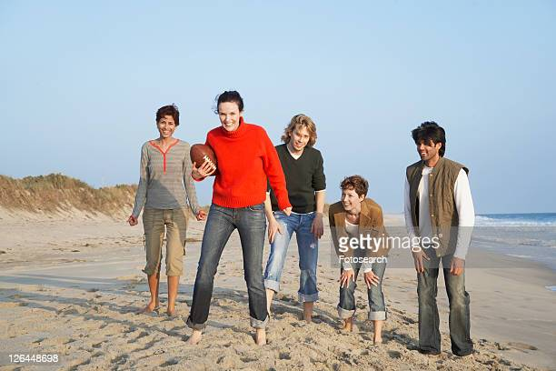 Five people with football standing on beach (portrait)