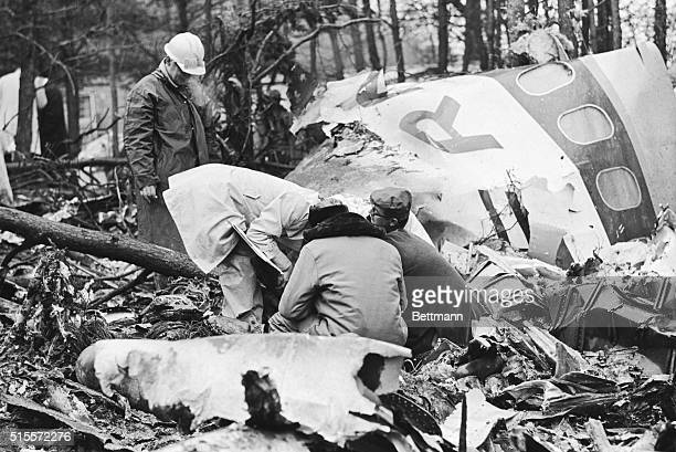 Five rescue workers search the wreckage of a plane crash in Huntington, West Virginia. The plane carried the entire Marshall University Football team...