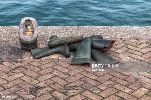 five rubber boots lie on the quay of the port - rubberlaars stockfoto's en -beelden