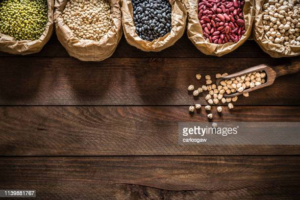 five rustic paper bags full of various types of legumes - bean stock pictures, royalty-free photos & images
