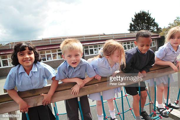 five school children in playground - britain playgrounds stock pictures, royalty-free photos & images
