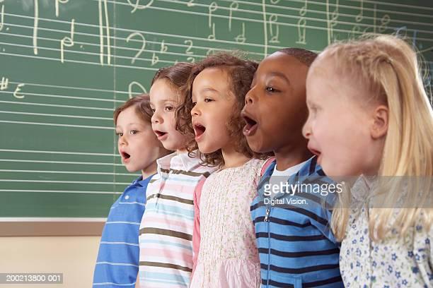Five school children (5-10) singing in class, close-up