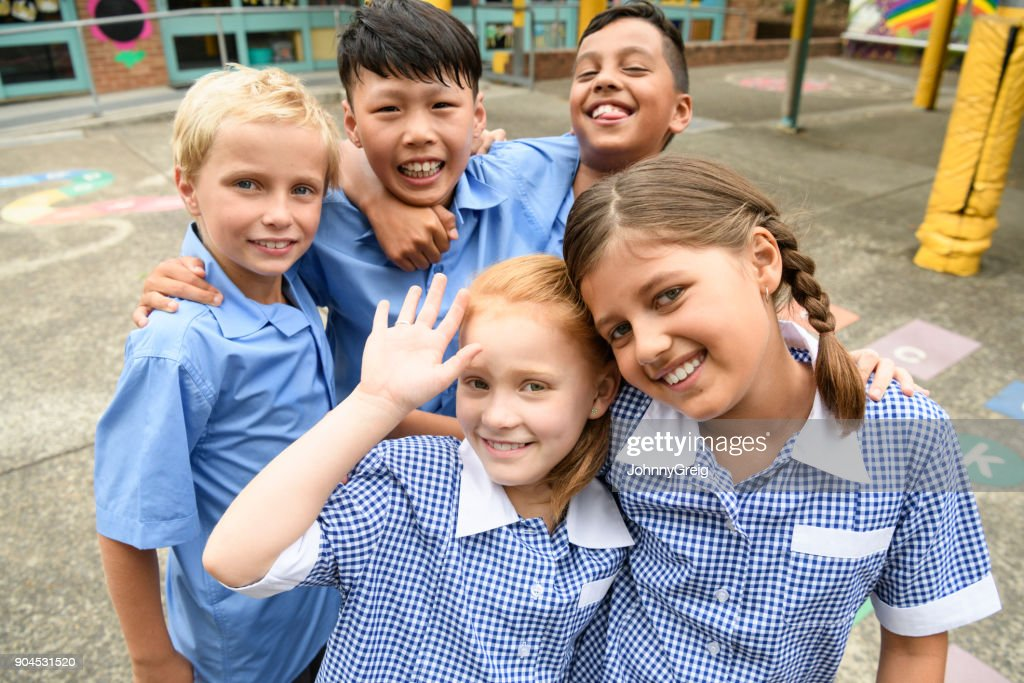 Five school friends posing for candid photo in playground : Stock Photo