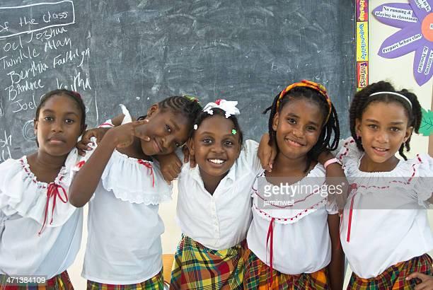 cinq schoolgirls heureux dans une salle de classe posant pour la caméra - écolière photos et images de collection