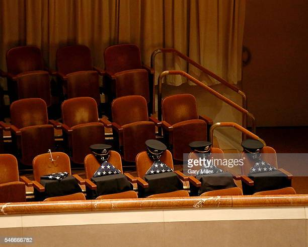 Five seats with folded United States flags are 'held' for the fallen policemen during the Interfaith Memorial honoring the Dallas shooting victims at...