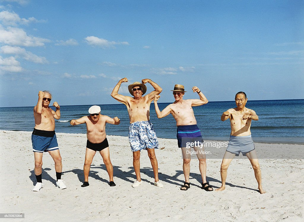 Five Senior Men in Swimming Trunks Stand on the Beach Flexing Their Muscles : Stock Photo