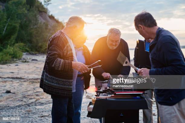 """five seniors brothers cooking fish on bbq on the beach - """"martine doucet"""" or martinedoucet stock pictures, royalty-free photos & images"""