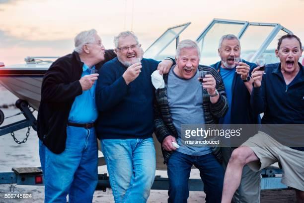 Fünf Senioren Brüder goofing um während der Happy Hour am Strand