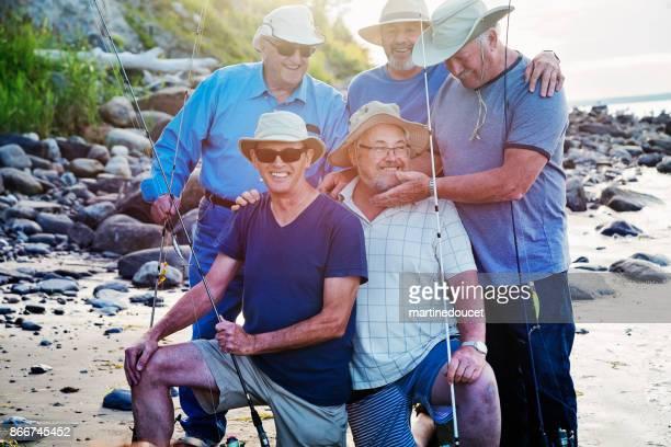 Fünf Senioren Brüder posiert auf einem Angeln Reise am Strand