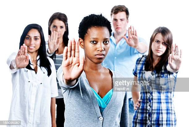 "Five serious young people indicate ""Stop""  holding up their hands"