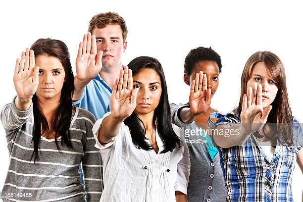 Five serious young people making Stop gesture