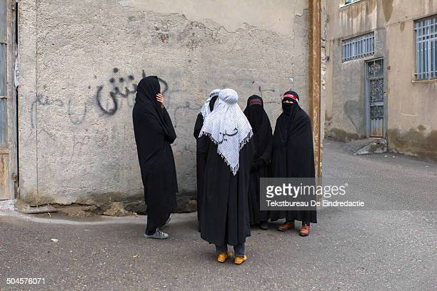 Five shiite muslim women, dressed in traditional black chadors and black veils, standing before a wall with Persian graffiti, on the streets of...