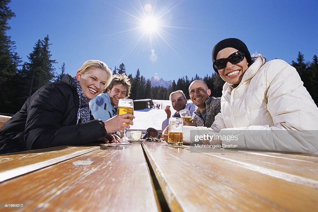 Five Smiling Friends at a Table With Lager in the Snowy Mountains : Stock Photo