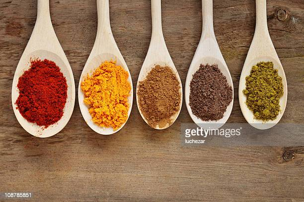 Five spoons with different colored spices