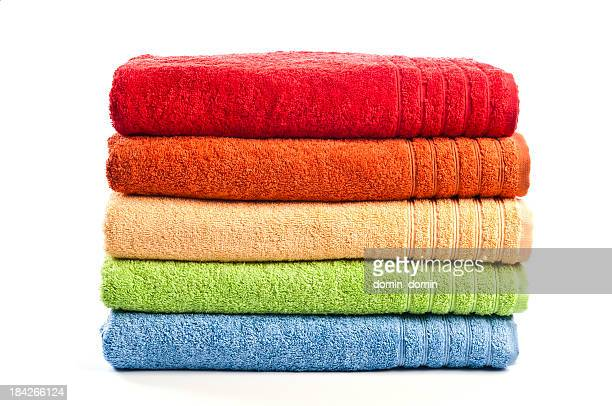 Five stacked, multicolored bath towels isolated on white background