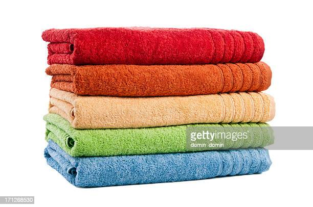Five stacked multicoloured bath towels isolated on white background, studio