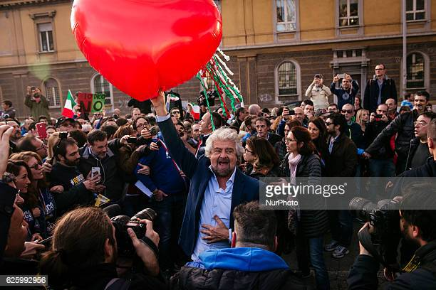 Five Stars movement's leader Beppe Grillo holds a heartshaped balloon during a demonstration for the upcoming constitutional referenda to be held on...
