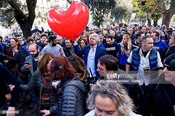 Five Stars movement's leader Beppe Grillo holds a heartshaped balloon during a demonstration for the upcoming Constitutional referendum to be held on...