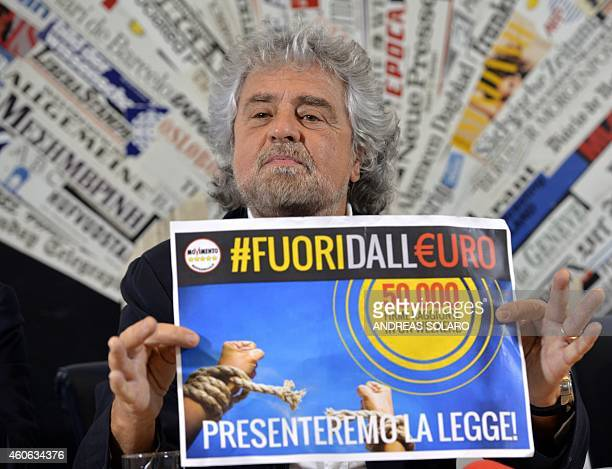 Five Stars movement's leader Beppe Grillo shows a paper reading 'Out of the Euro 50000 signatures in a weekend' during a press conference on December...